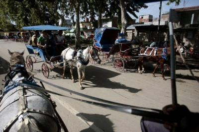 Habitantes de la ciudad de Bayamo, en la oriental provincia cubana de Granma, utilizan los coches tirados por caballos como transporte público.