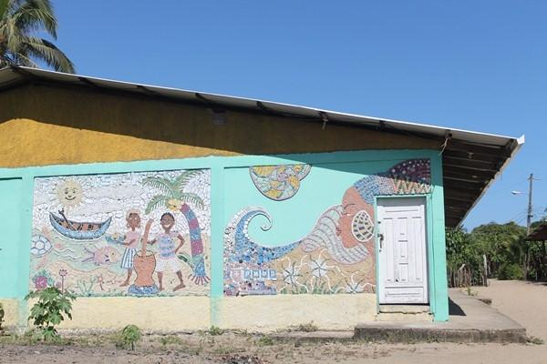 La frasque faite de morceaux de plastique et d'autres matériaux recyclables réalisée sur le mur du centre de la communauté par les habitants de Santa Rosa de Aguán pour célébrer leur mode de vie et la beauté des femmes Garífuna, et de rappeler à la ville la nécessité d'atténuer les changements climatiques.