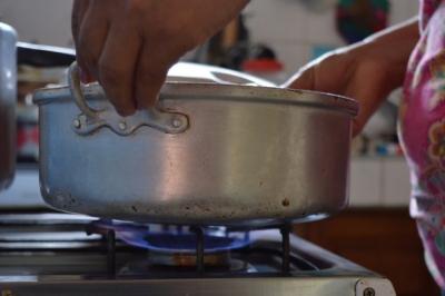 La médica rural Arianna Toledo calienta agua en su cocina a biogás en su vivienda de Cuatro Esquinas, en el municipio Los Arabos, en Cuba.