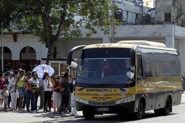 Pasajeros abordan un microbús de una cooperativa de transporte urbano que cubre varias rutas entre varios municipios de La Habana.