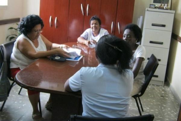 Miriam Fernández, de espaldas, conversa con especialistas del Taller de Transformación Integral del Barrio de Pogolotti, en el oeste de La Habana
