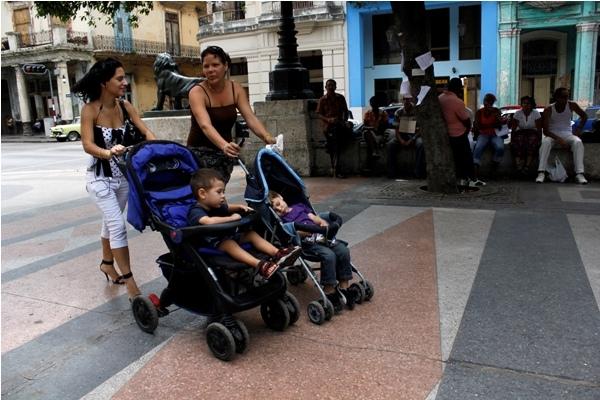 Dos jóvenes madres cubanas pasean con sus hijos por una avenida de La Habana.