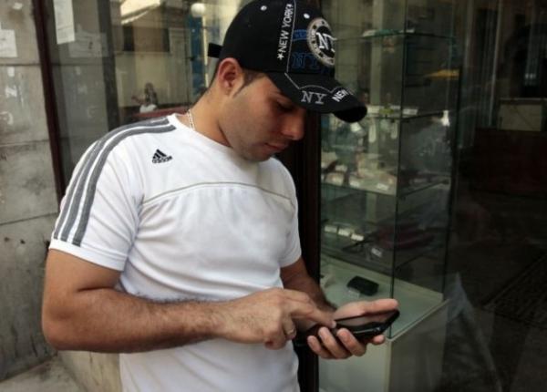 Un joven cubano, luciendo un gorro con inscripciones de Nueva York y una camiseta de la marca Adidas, consulta su teléfono celular en La Habana.