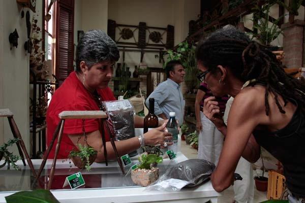 La vendedora explica a una clienta las bondades y maneras de usar un biofertilizante.