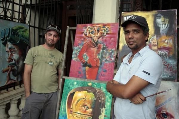 Carlos González, a la izquierda, y Eloy Milán, integrantes del proyecto artístico Open Art Studio, posan junto a sus obras en su taller en una céntrica calle frente al malecón de La Habana, en Cuba.