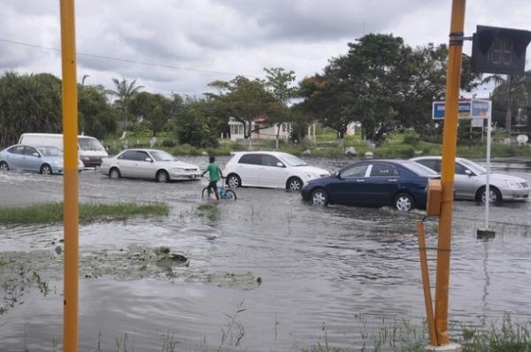 Un joven camina con su bicicleta por una calle inundada en Georgetown, la capital de Guyana.