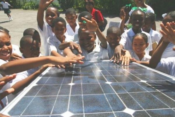 Niños y niñas aprenden sobre energía solar durante una exhibición en Georgetown, Guyana.